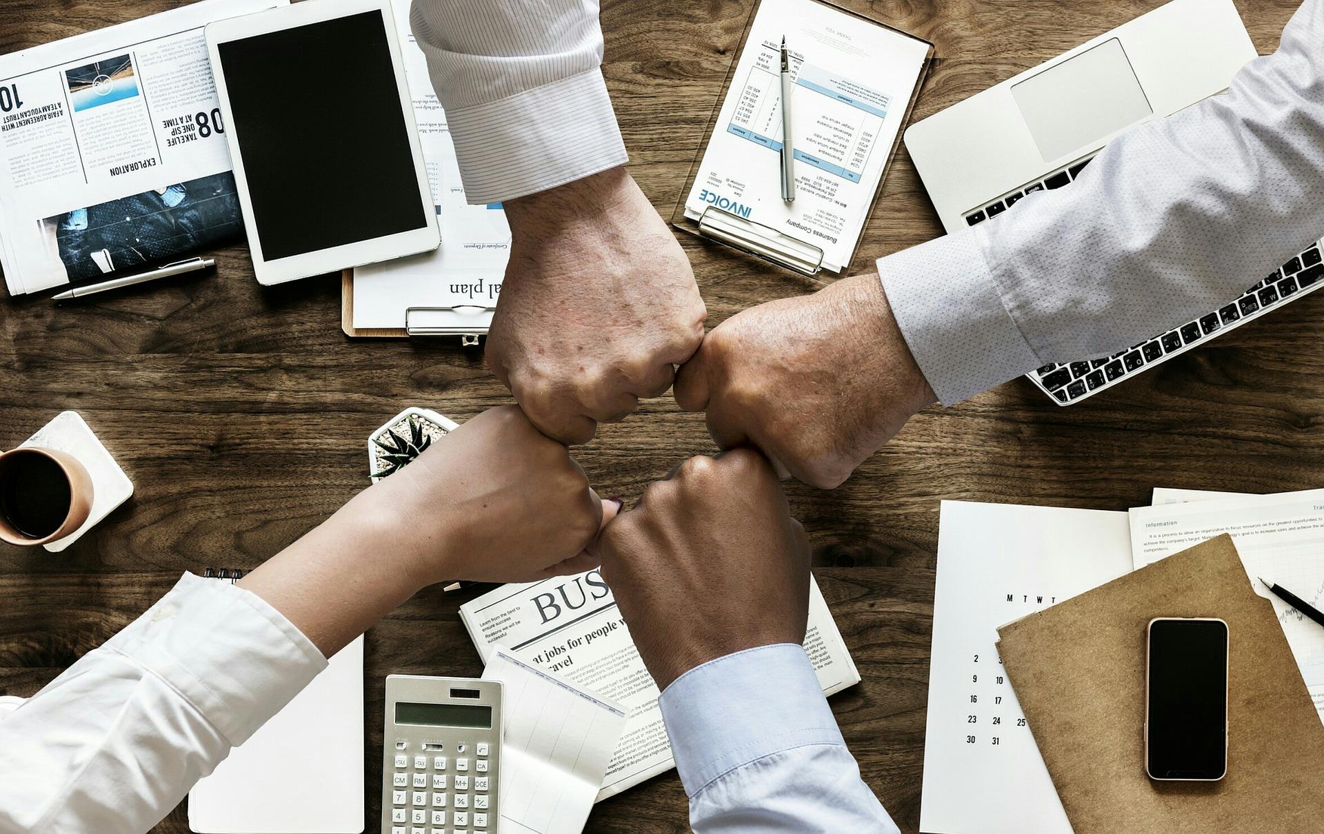 4 puños mostrando unidad de equipo en una oficina.